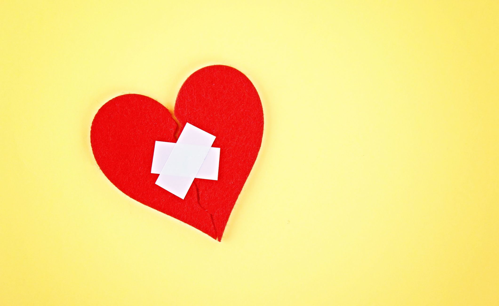 A red felt heart broken into two halves, glued together by a plaster on a yellow background.