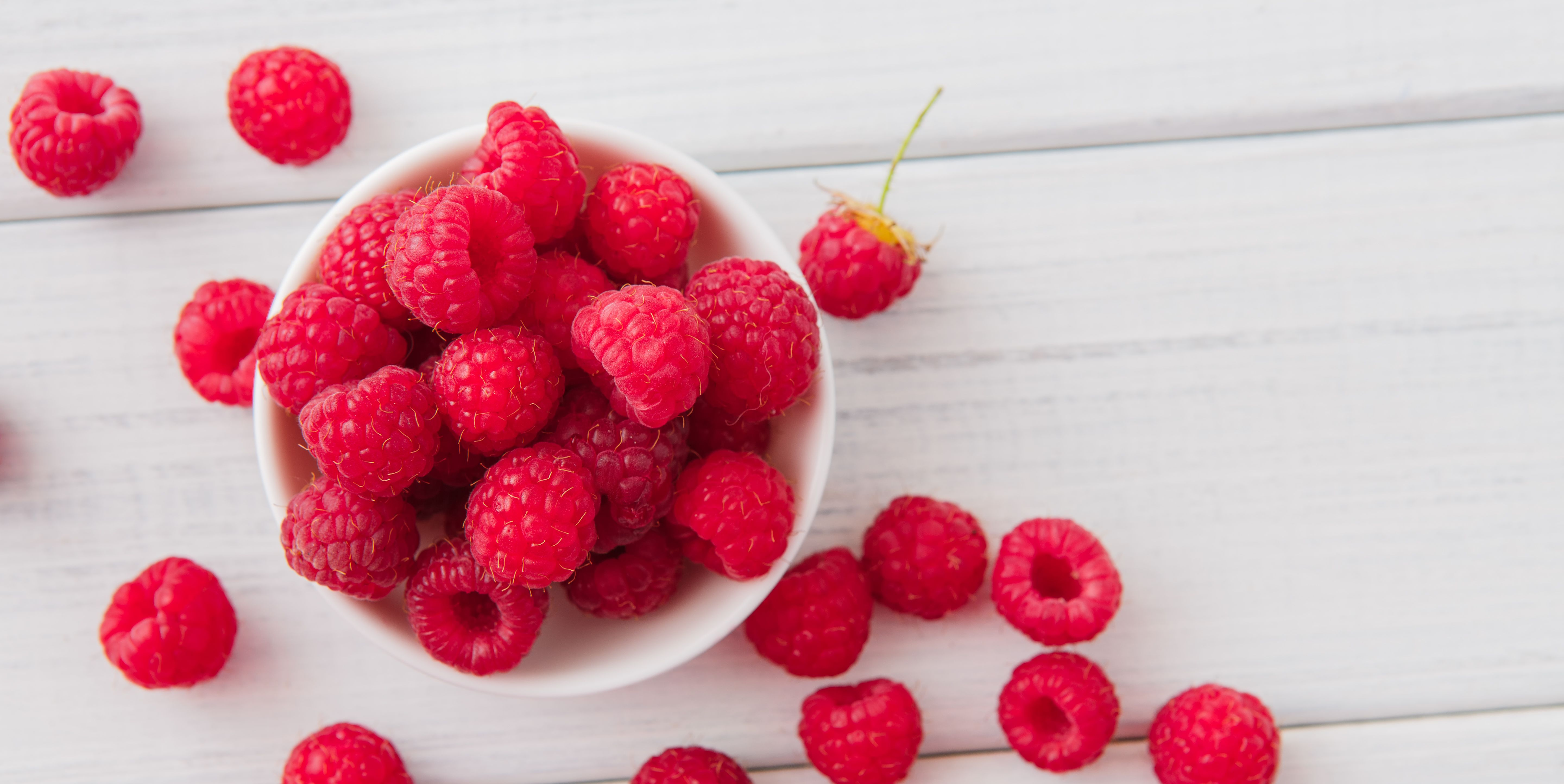 Red fresh raspberries on white rustic wood background