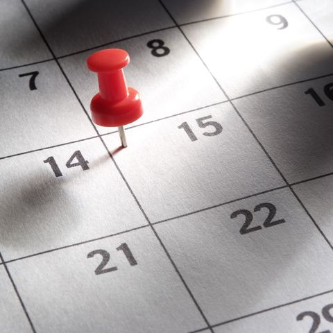 Red thumbtack in calendar with light rays