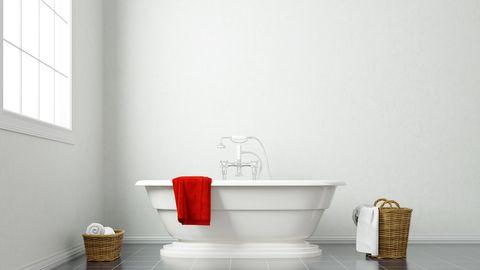 Red Towel On Bathtub Against White Wall In Bathroom