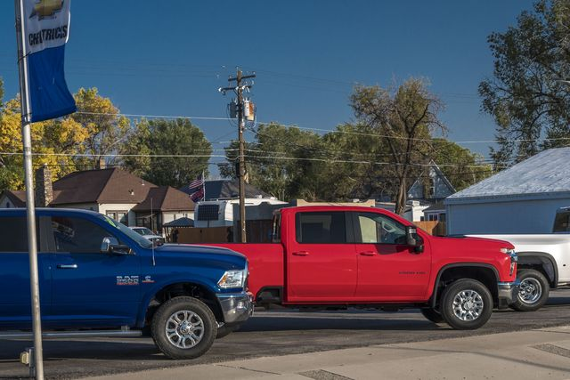 red white and blue american pickup trucks on lot in delta, colorado