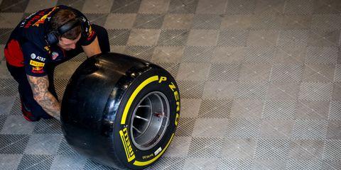 redbull mechanic working in a pirelli wheel during the