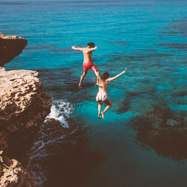 man and woman jumping off cliff into ocean