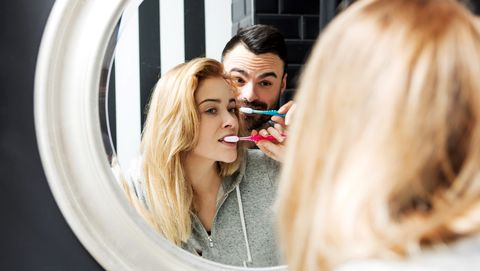 Reflection Of Couple Brushing Teeth In Mirror At Bathroom