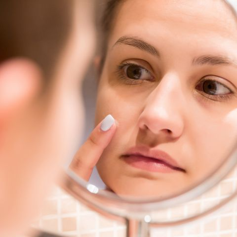 reflection of woman applying moisturizer on pimple in mirror at home