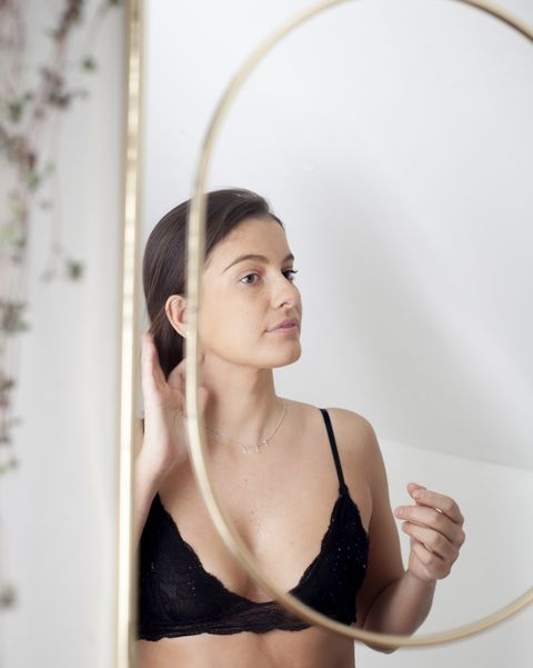 reflection of woman in bra in mirror during morning preparation