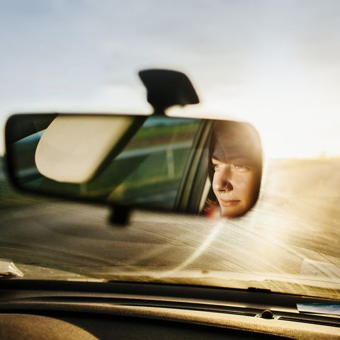 reflection of woman in rear view mirror