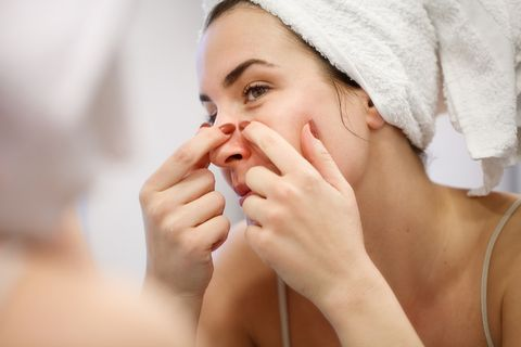 reflection of woman with towel on head squeezing blackhead on her nose side