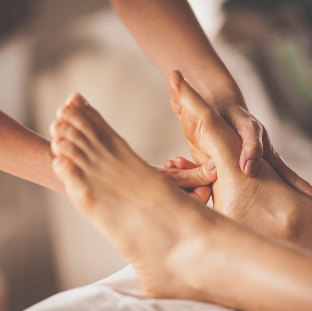 reflexologist applying pressure to foot with thumbs
