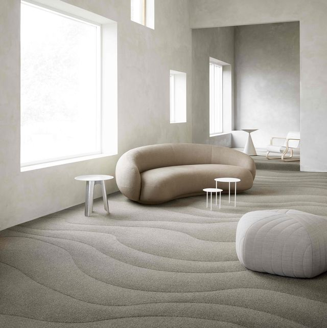 curved sofa and curvy carpet in neutral room
