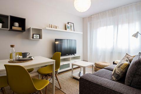 salón comedor de estilo nórdico con sofá gris, muebles blancos y sillas mostaza
