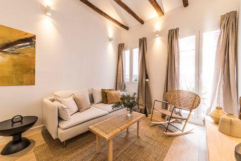 salón con vigas de madera vistas y decoración natural en tonos blancos y tostados