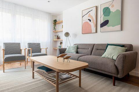 salón de estilo contemporáneo con sofá y butacas grises y mesa de centro de madera