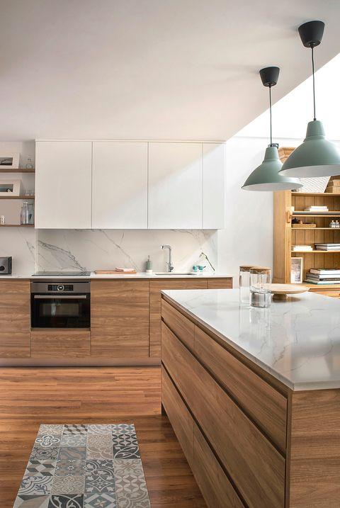 cocina con isla central, revestimientos efecto mármol y armarios de madera sin tiradores