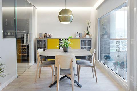 comedor de diseño moderno con mesa y sillas de madera y lámpara de techo dorada