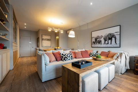 salón open concept decorado con suelo y mesa de centro de madera, sofá gris y cojines en tonos teja