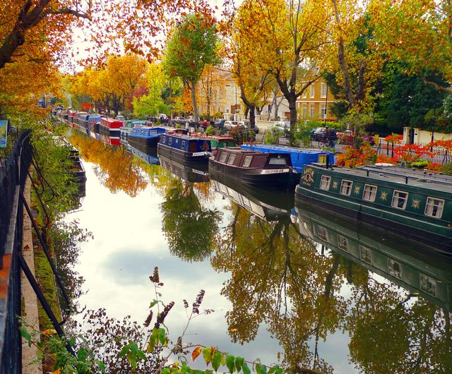 autumnal scene on regent canal in london with the boats and painter