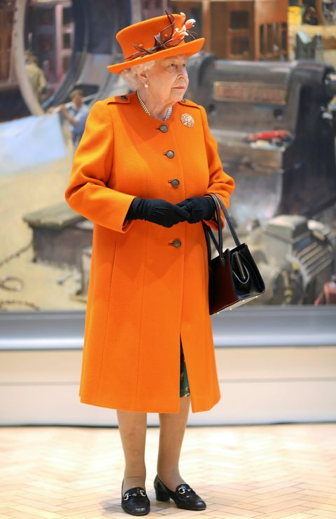 Clothing, Street fashion, Orange, Fashion, Overcoat, Yellow, Coat, Standing, Outerwear, Trench coat,