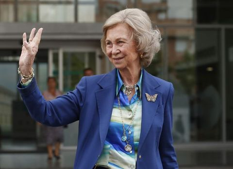 la reina sofia saludando sonriendo con la mano levantada en la calle