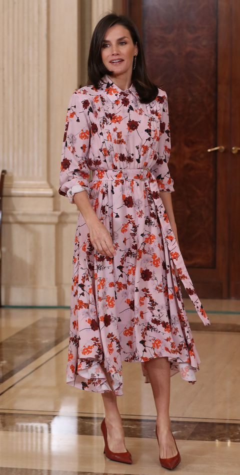 la reina, con un vestido rosa con estampado de flores, en una audiencia