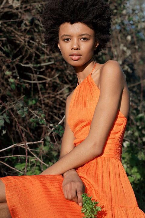model sitting amongst trees in orange halterneck dress holding small green stems