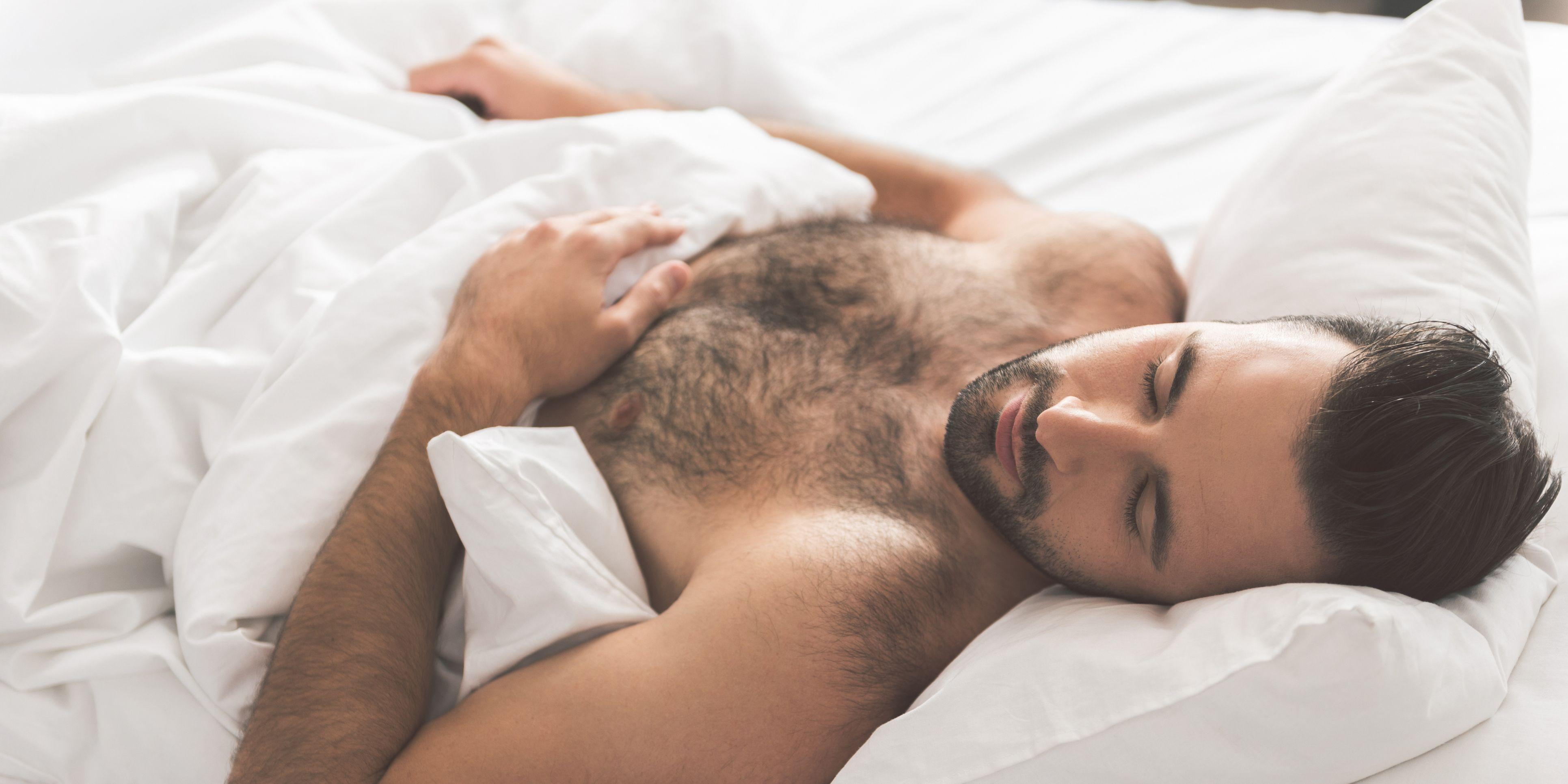 Relaxed guy having nap on white bedding