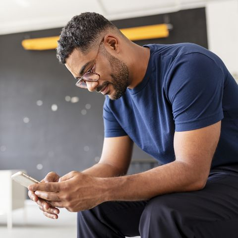 relaxed man sitting on a chair and using  cell phone