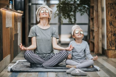 Relaxed mother and daughter exercising Yoga in the morning at home.