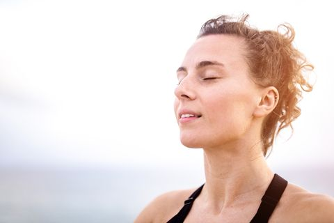 relaxed young woman meditating outdoors by the sea head close up