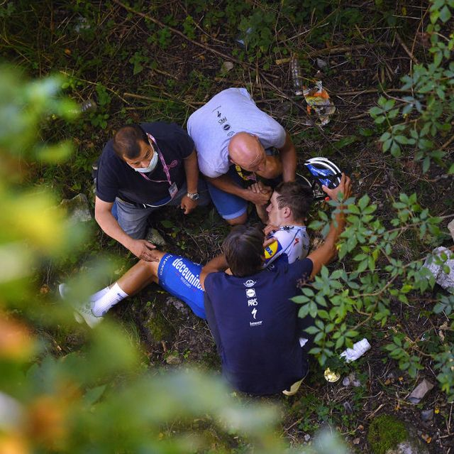 evenepoel lying in a ravine, surrounded by medics, after crashing into a stone wall at the 114th il lombardia 2020
