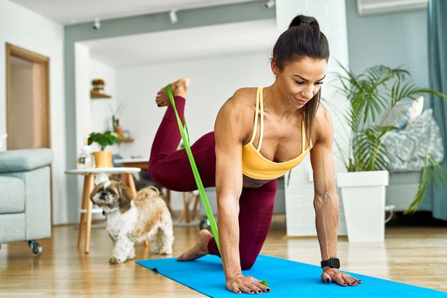 young muscular build woman doing leg resistance band exercises while working out in the living room