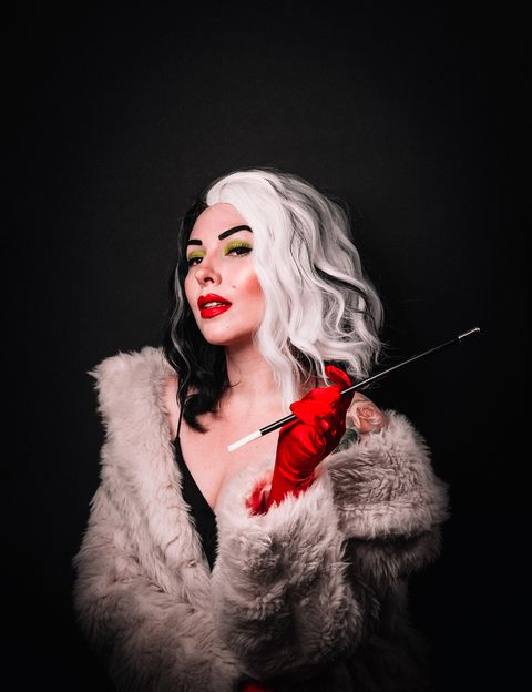 woman dressed as cruella de vil with red satin gloves, white faux fur, cigarette holder and halfwhite, halfblack wig