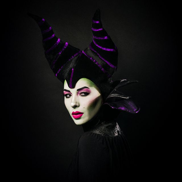 woman dressed as maleficent with sharp cheekbones, purple head dress and horns and collar