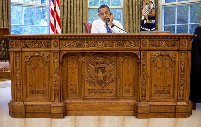 president barack obama sitting at the resolute desk in the oval office of the white house