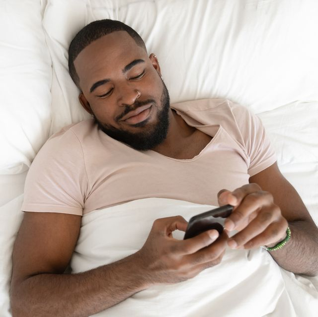rested african american man waking up at comfortable bed