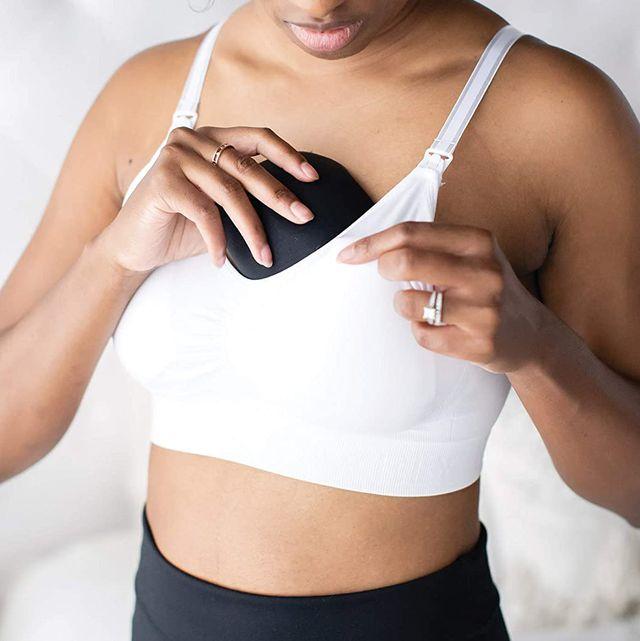 woman putting reusable nursing pad in bra