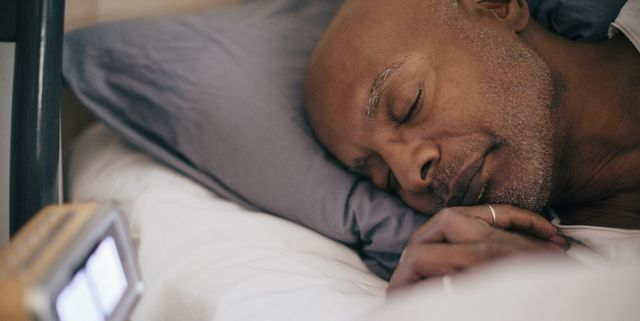 retired senior man sleeping on bed by alarm clock at home