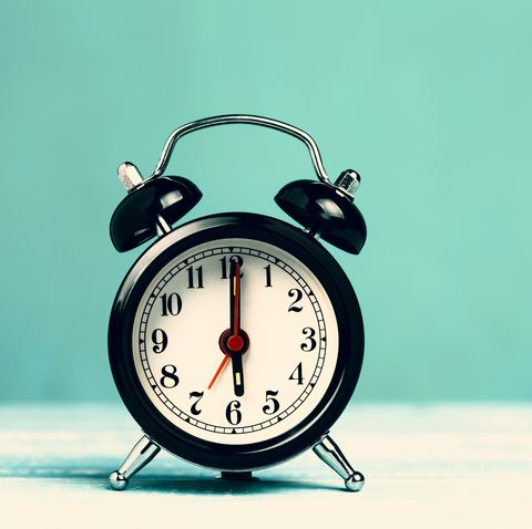 retro black alarm clock on turquoise background with copy space alarm at 7 o'clock clock hand at 6 o'clock