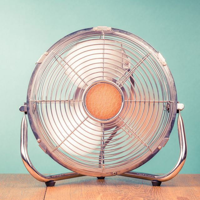 retro portable office or home cooling fan in working mode standing on table vintage instagram style filtered photo