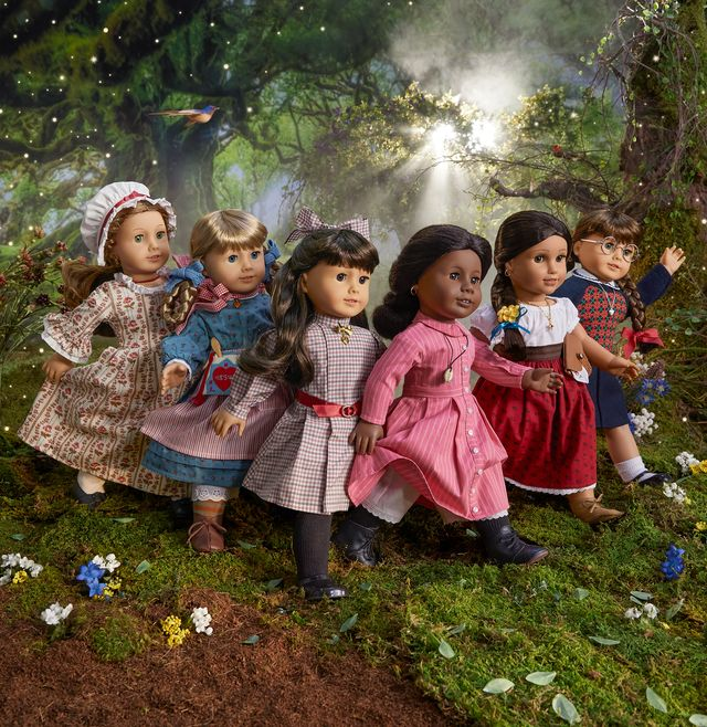 a photo of six american girl dolls in historical outfits