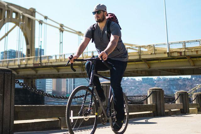 man wearing dark medium revtown jean riding bicycle
