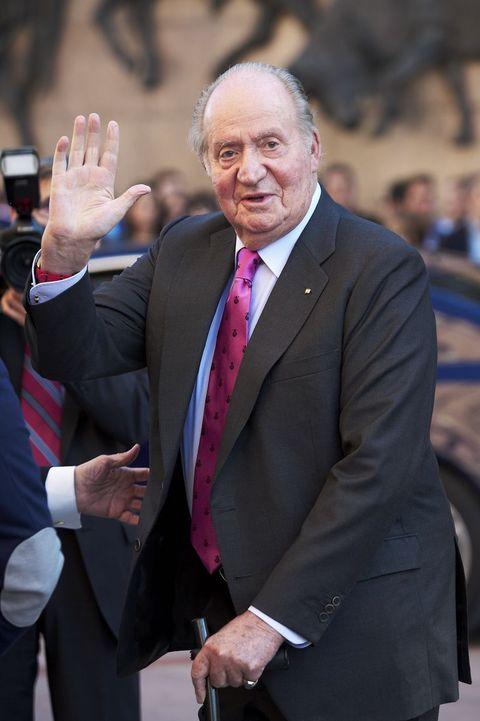 el rey juan carlos saludando con la mano levantada en la calle