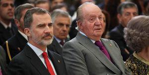 Rey Juan Carlos y el rey Felipe VI sentados y serios.