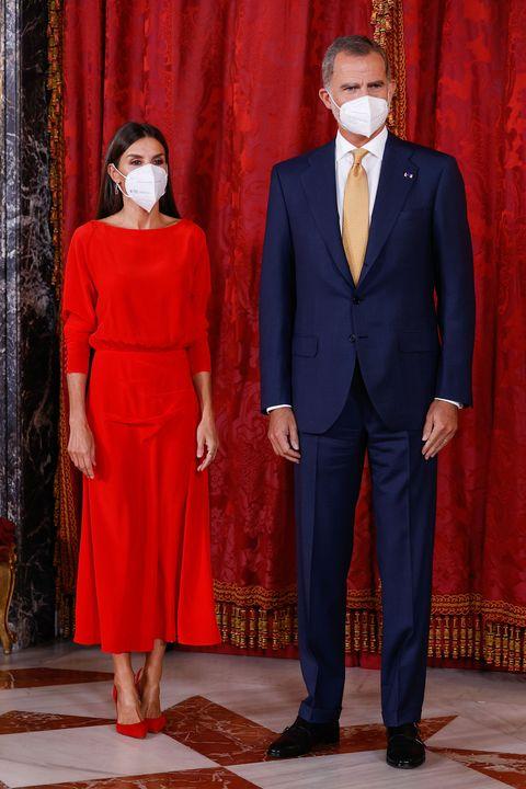 doña letizia, con un vestido rojo de massimo dutti, y felipe vi, con traje, en el palacio real de madrid