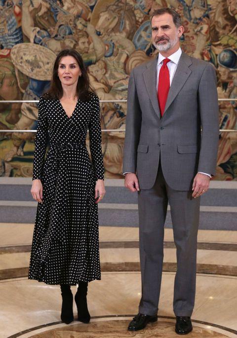 los reyes, ella con un vestido de lunares y él con traje gris y corbata roja, en uno de los salones del palacio real