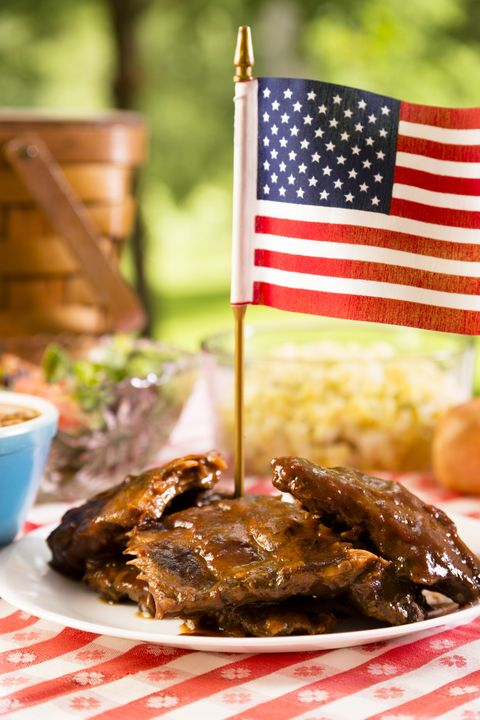 bbq ribs topped by american flag, beans, potato salad on a red and white table cloth