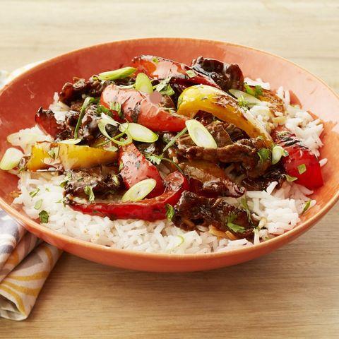 hoisin steak and pepper stir fry over rice in orange bowl