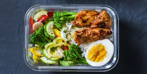 Rice, stewed vegetables, egg, teriyaki chicken - healthy balanced lunch box on a dark background, top view. Home food for office concept