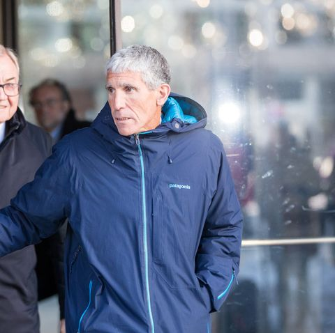 rick singer exiting a courthouse wearing a blue patagonia jacket