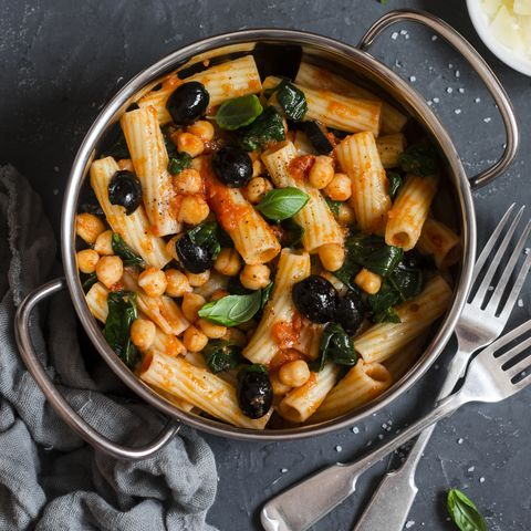 Rigatoni pasta with chickpeas, spinach and olives in a tomato sauce on a dark background, top view. Vegetarian food concept